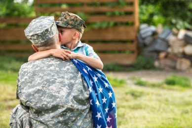 Military Family Hugging with Flag